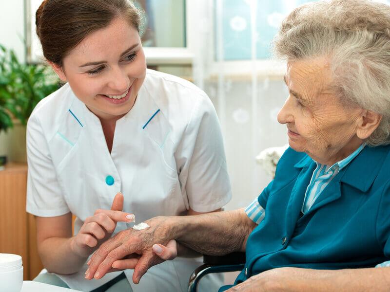 Pflegerin cremt Haut einer Seniorin zur Dekubitusprophylaxe ein