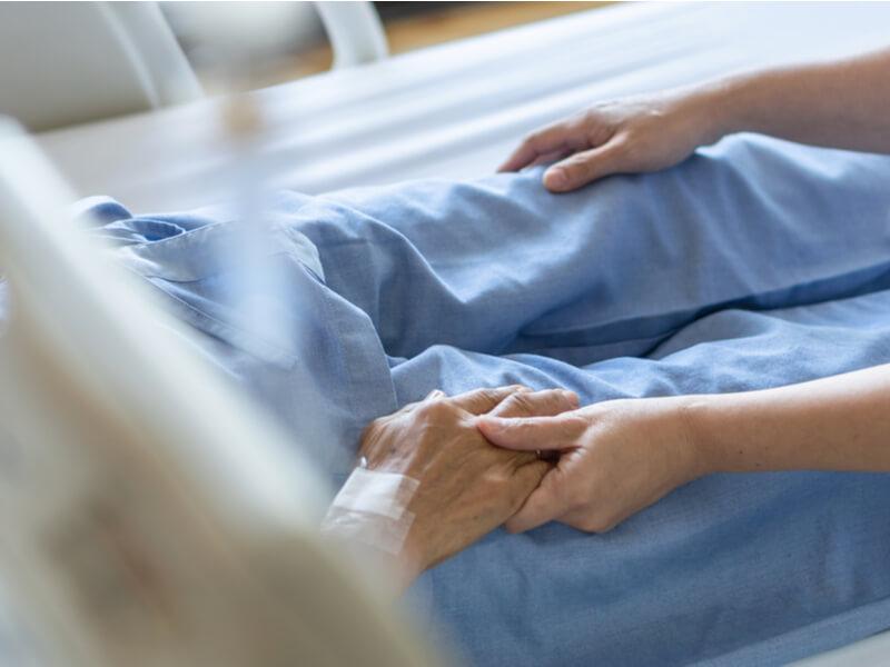 Die Hand eines bettlägerigen Pflegebedürftigen wird von einer anderen Person gehalten