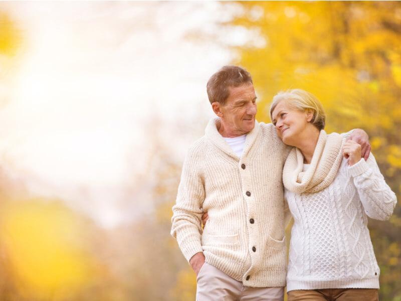 Paar im mittleren Alter beim Spaziergang durch den Herbstwald