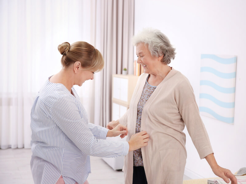 Pflegende Angehörige hilft Seniorin beim Anziehen