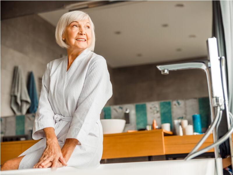 Ältere Dame in weißem Bademantel sitzt auf Badewannenrand
