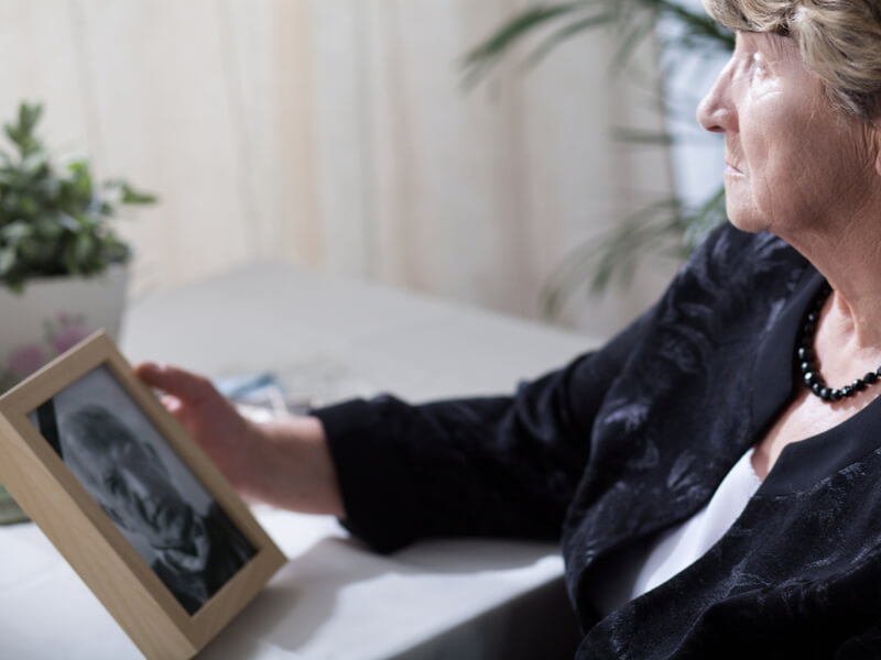 Ältere Frau schaut auf Bild eines verstorbenen Mannes