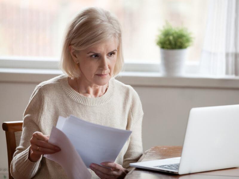 Blonde Frau mittleren Alters mit Dokumenten und Laptop