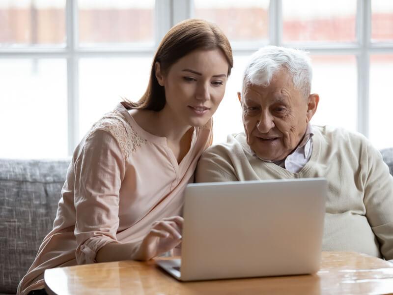 Junge Frau hilft älterem Herren beim Erstellen einer Vorsorgevollmacht