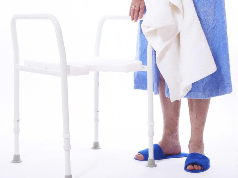 Duschhocker an dem sich ein Senior festhält