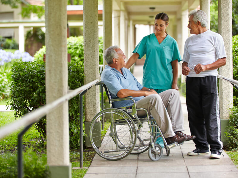 Mann im Rollstuhl, Pflegerin und Mann in Sportkleidung vor Altersheim