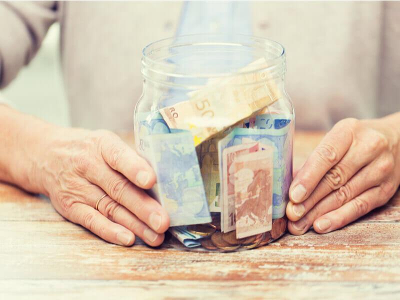 Frau hebt Rückkaufswert in einem Glas auf.