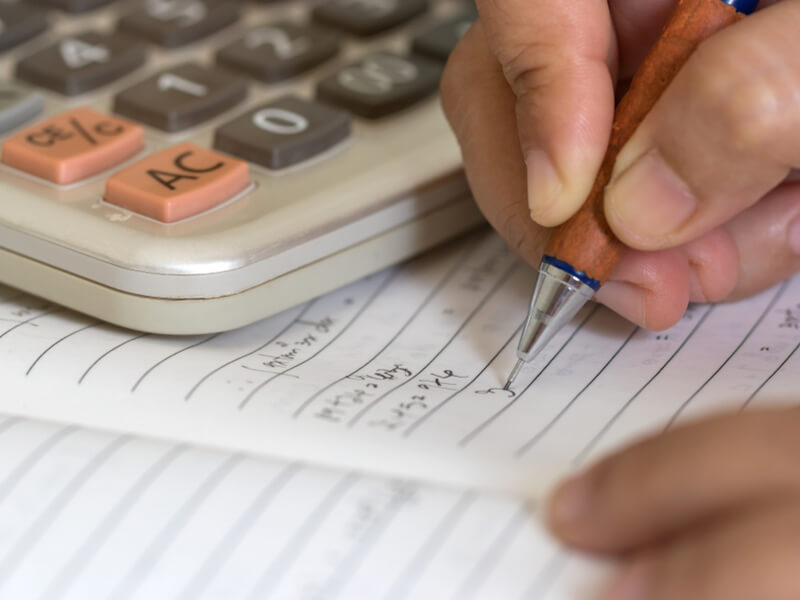 Taschenrechner und Hand, die ins Notizbuch schreibt