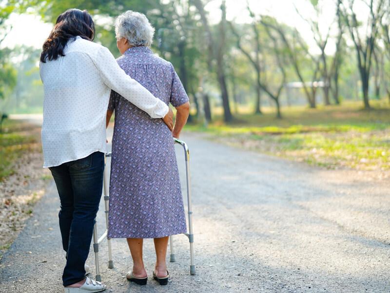 Verhinderungspflege: Pflegerin hilft Seniorin beim Spaziergang