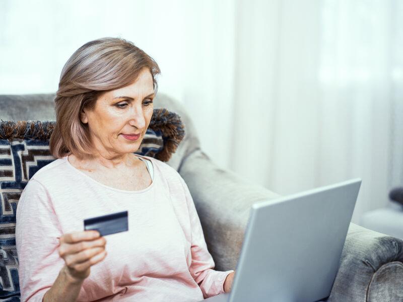Frau mit Notfallkarte vor Laptop