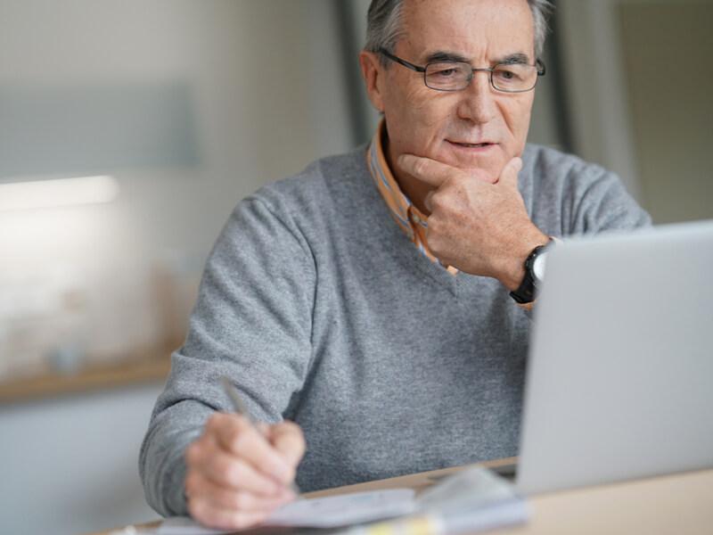 Älterer Herr mit Brille am Laptop