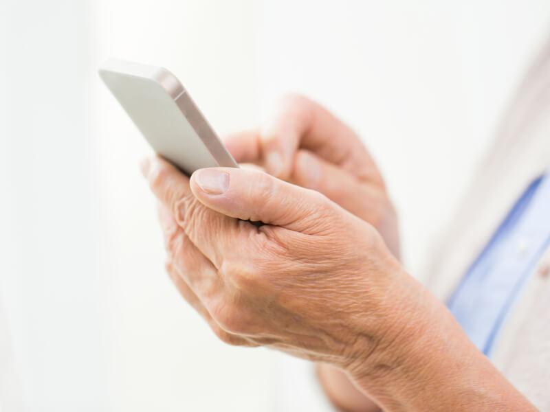 Nahaufnahme von Händen mit Seniorenhandy