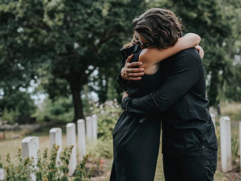 Mann tröstet Frau nach Todesfall