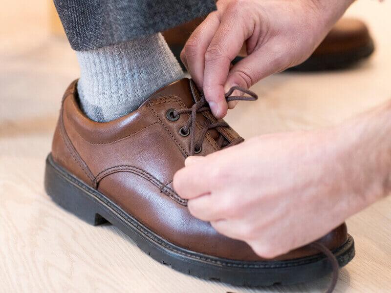 Häusliche Pflege: Angehöriger hilft Pflegebedürftigem beim Schuhe zubinden.