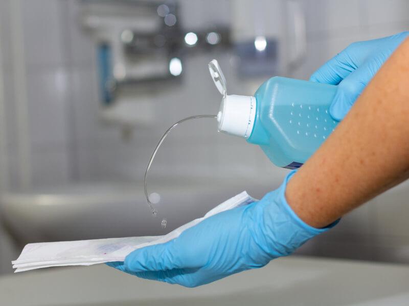 Nahaufnahme von Händen, die mit Schutzhandschuhen und Desinfektionsmittel eine Fläche reinigen