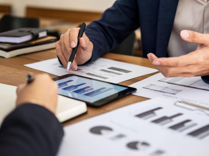 Dokumente und Tablet auf dem Tisch eines Beraters im Gespräch