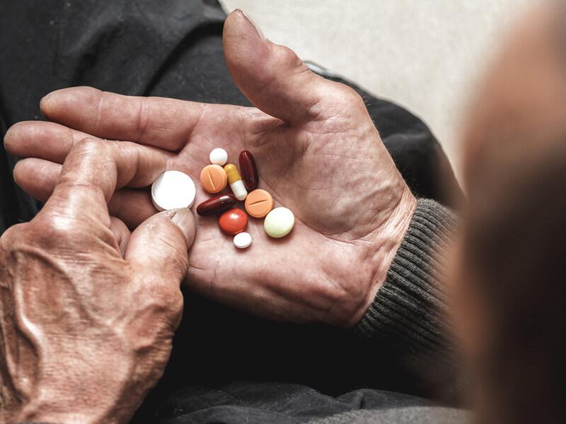Alter Mann mit Multimorbidität hält verschiedene Medikamente in der Hand