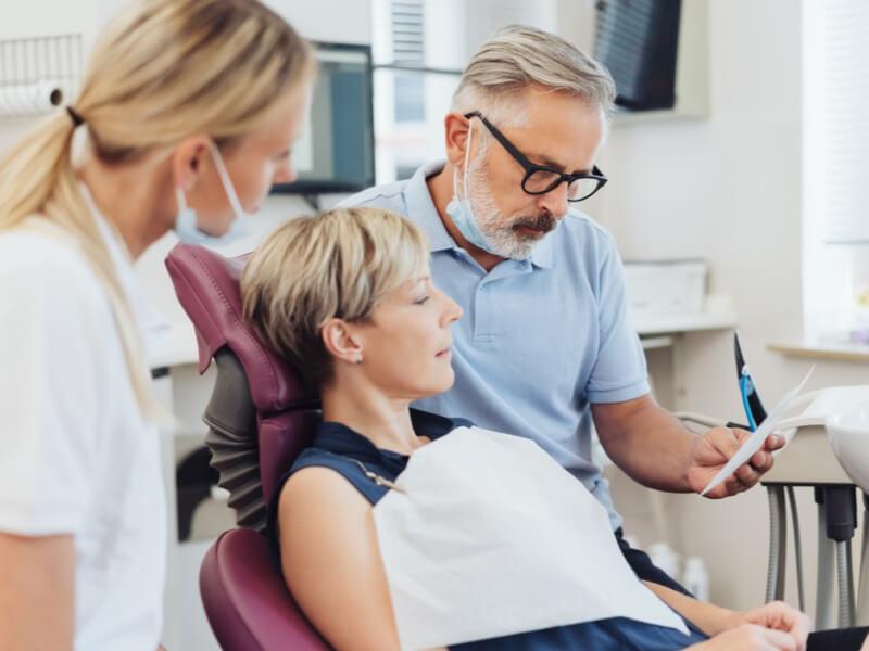 Patientin auf Zahnarztstuhl mit Arzt und Assistentin bei der Besprechung des Befunds