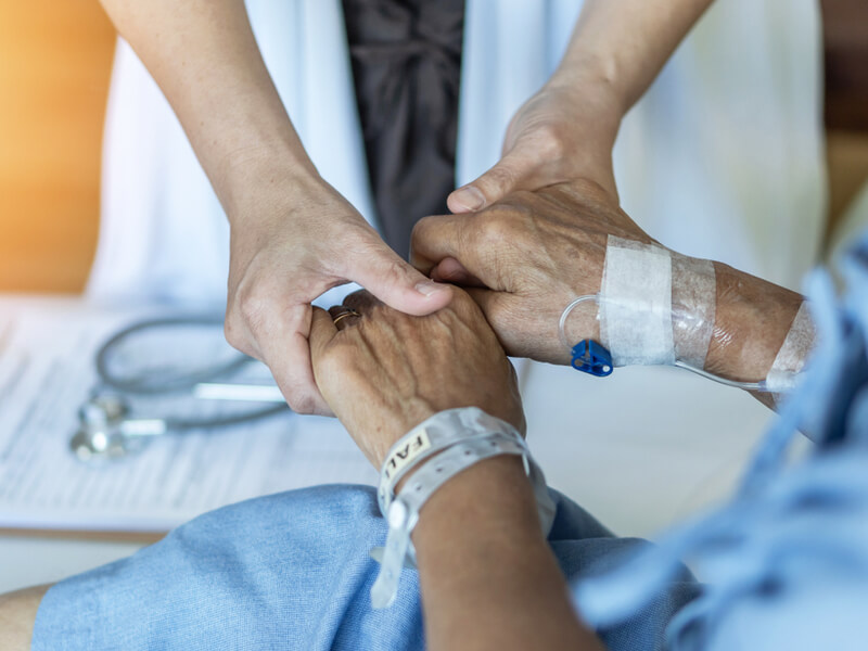 Ärztin hält beide Hände eines Patienten