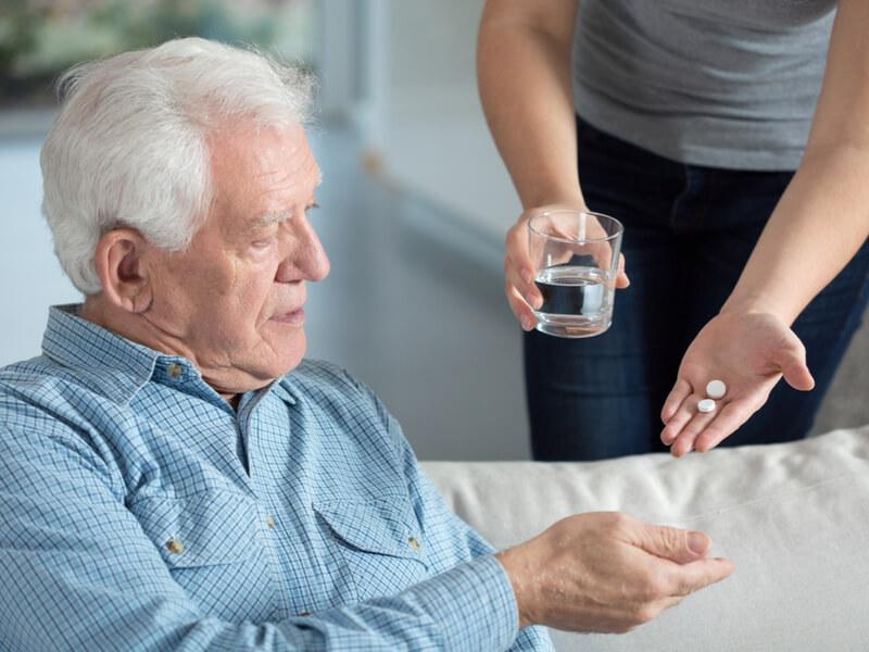Pflegende Angehörige reicht einem älteren Mann seine Tabletten und ein Glas Wasser
