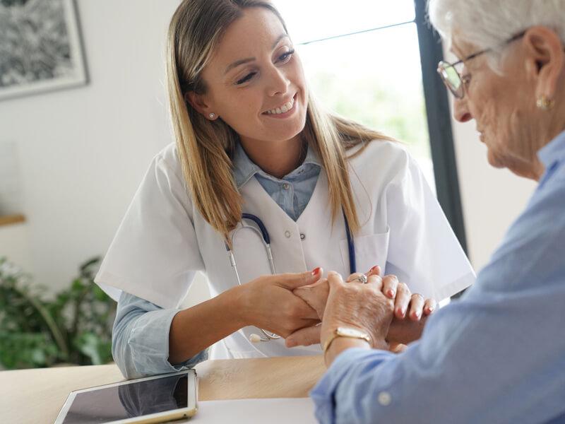 Krankenpflegerin pflegt Seniorin