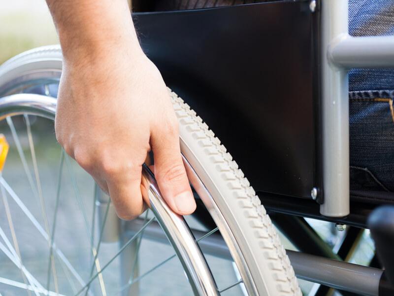 Nahaufnahme der Hand eines Rollstuhlfahrers, die den Reifen bewegt