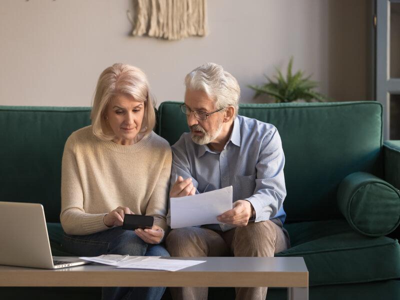 Lebensversicherung verkaufen: Ehepaar berät auf Couch über den Verkauf