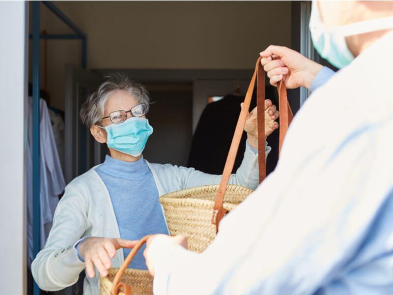 Ältere Dame mit Mundschutz nimmt an der Haustür Einkäufe von Helfer entgegen