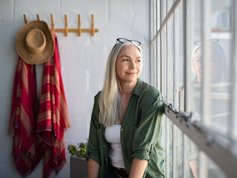 Frau im mittleren Alter mit langen, weißen Haaren schaut aus dem Fenster