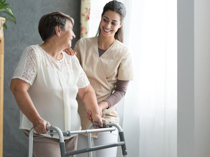 Entlastungsbetrag: Seniorin mit Rollator und Pflegefachkraft