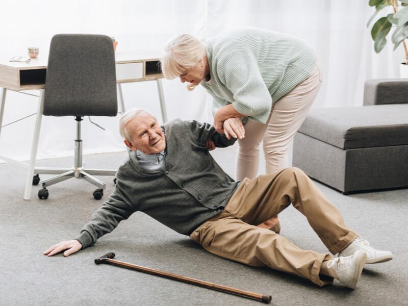 Unfallversicherung sinnvoll für Senioren: Frau hilft gestürztem Senior auf