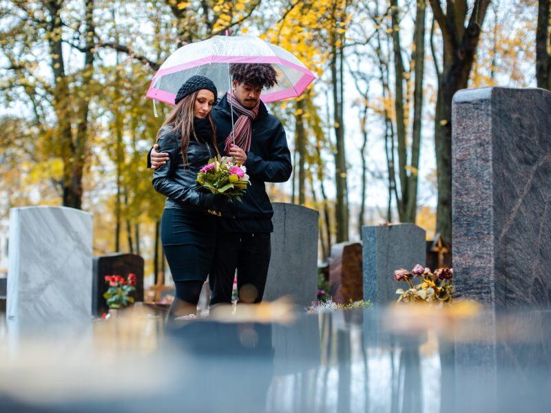 Zwei Angehörige besuchen ein Grab von einem Erblasser auf einem Friedhof