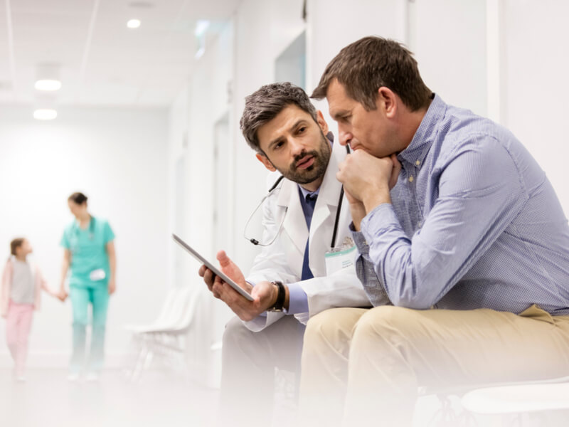 Arzt im Krankenhaus spricht mit dem Angehörigen eines Patienten